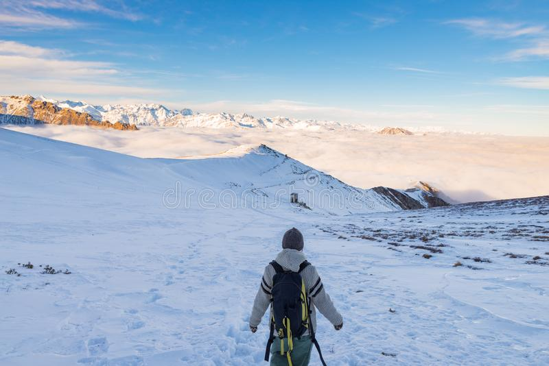 Backpacker hiking on snow on the Alps. Rear view, winter lifestyle, cold feeling, majestic mountain landscape. royalty free stock photos