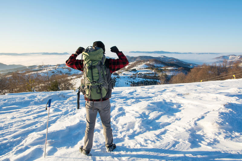 Backpacker hiking on snow covered mountain. Winter active time stock photo