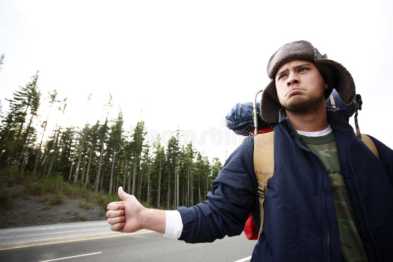 Backpacker hitchhiking. A backpacker hitchhiking on a mountain road stock photos