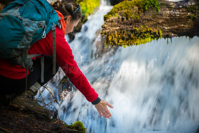 Backpacker holding hand under running water of clearwater falls royalty free stock image