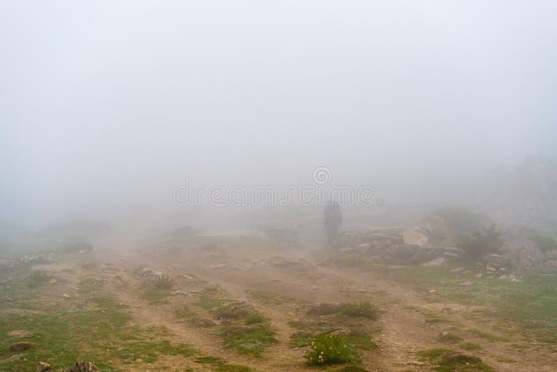 Backpacker irreconocible en la trayectoria de niebla en área de la protección de Annapurna, Nepal del senderismo imagen de archivo libre de regalías