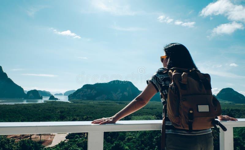Backpacker joven feliz de la mujer del viajero que mira la montaña con el mar y que goza de un hermoso de la naturaleza en, pasió fotografía de archivo