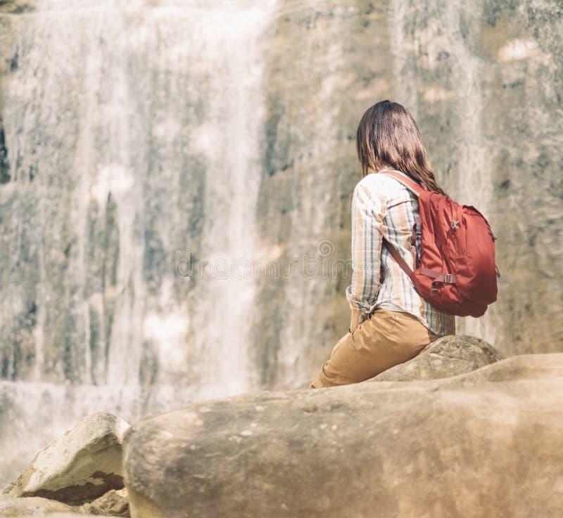 Backpacker kobieta patrzeje siklawę na słonecznym dniu zdjęcie stock