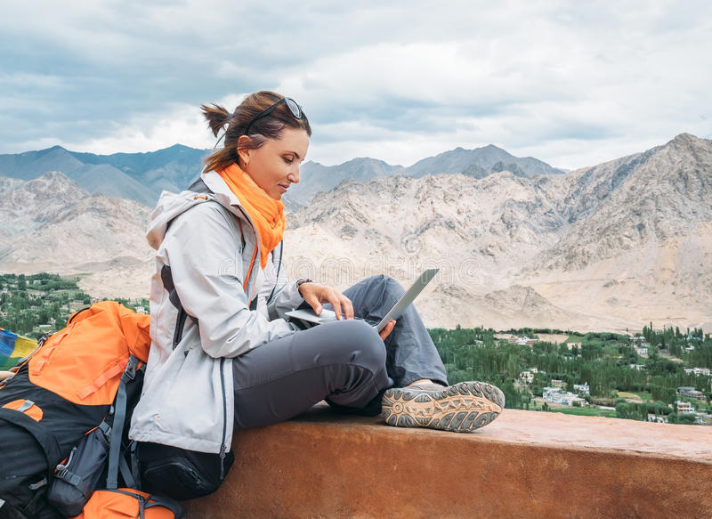 Backpacker with laptop sits on the top view point under mountain. Settelment royalty free stock photos
