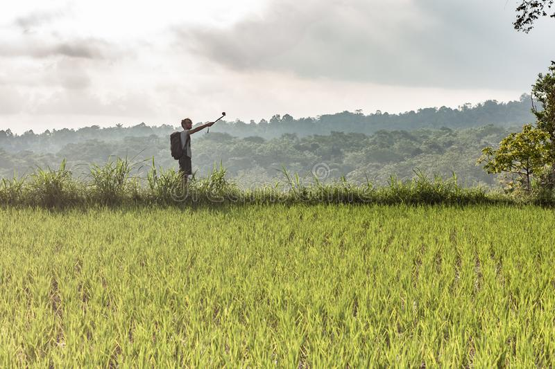 Backpacker makes selfie among rice fields on a cloudy day. Backpaker makes selfie among rice fields on a cloudy day royalty free stock image