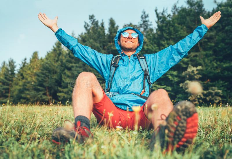 Backpacker man has a rest break enjoying mountain landscape wide opened and raised arms. He wears in blue rain coat poncho and stock photography