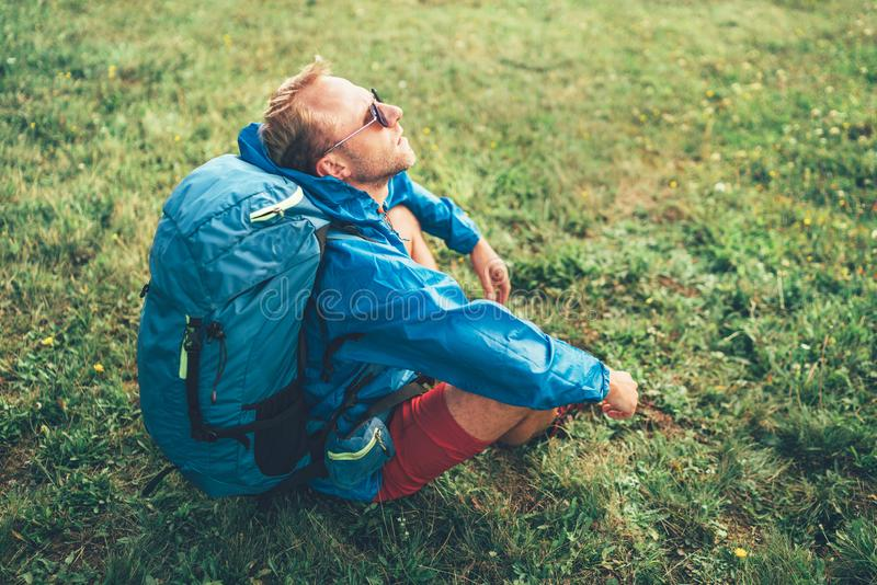 Backpacker man has a rest break sitting on green grass and enjoying mountain walking, he raised his head into air.  Active sports royalty free stock images