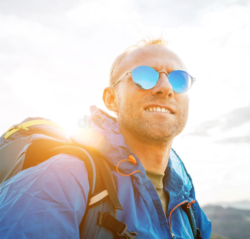 Backpacker man lifestyle portrait enjoying mountain landscape. He wears in blue rain coat poncho and blue sunglasses. Active royalty free stock photo