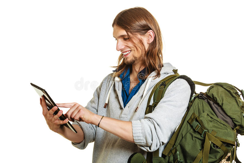 Backpacker man using pc tablet browsing internet. royalty free stock photos