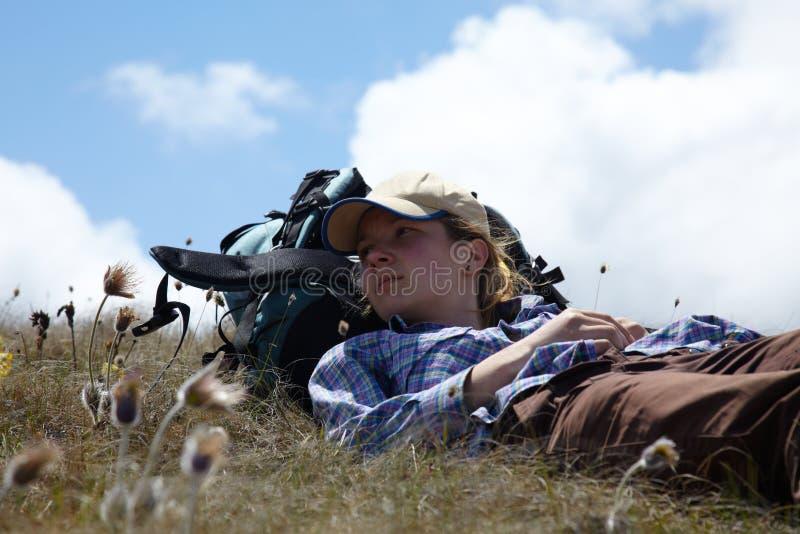 Backpacker relahing on a meadow