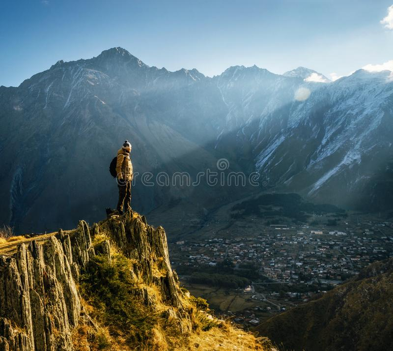 Backpacker sit on cliff edge and looks at mount valley. Young tourist in bright hat, black trousers with a backpack stands on cliff`s edge and looking at the royalty free stock image