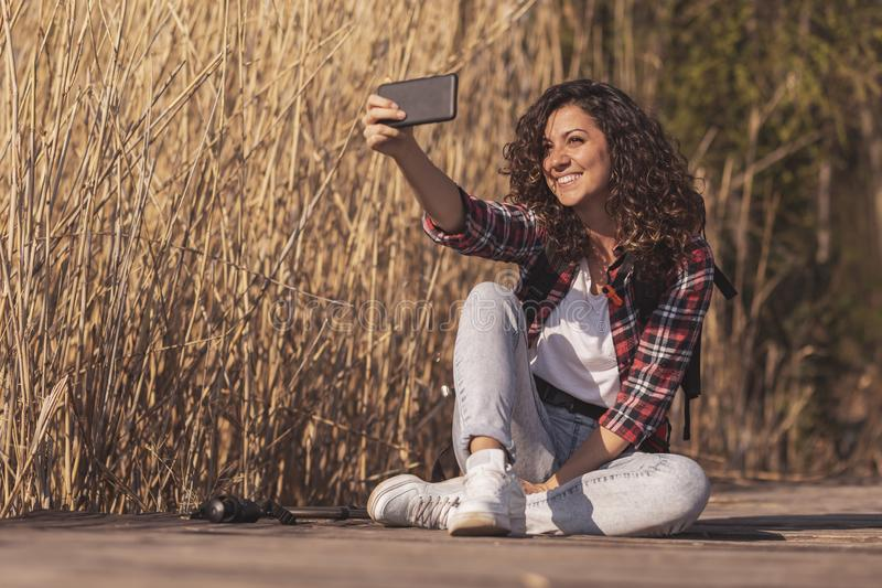 Backpacker taking a selfie. Woman sitting on the wooden lake docks, taking a break from hiking in nature, relaxing and taking a selfie stock photo