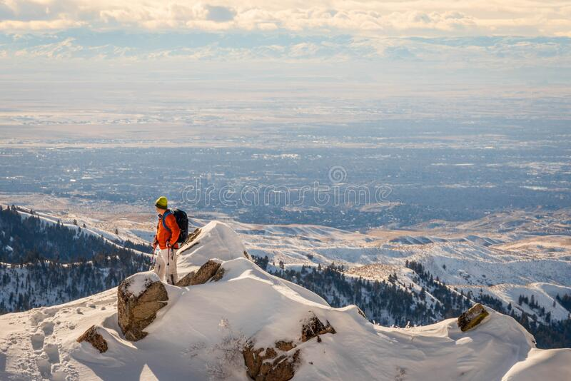 Backpacker on top of a snowy mountain overlooking the city. Backpacker on top of a snowy mountain overlooking Boise, Idaho during winter royalty free stock photography