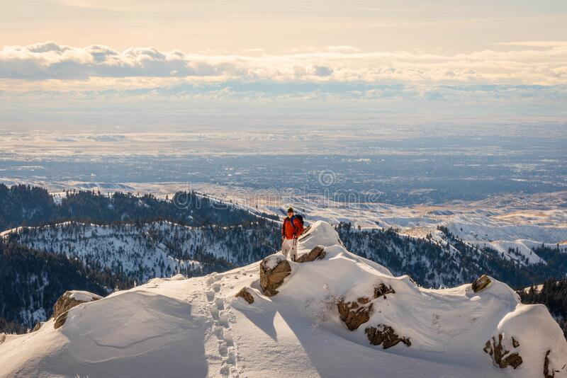 Backpacker on top of a snowy mountain overlooking the city. Backpacker on top of a snowy mountain overlooking Boise, Idaho during winter stock images
