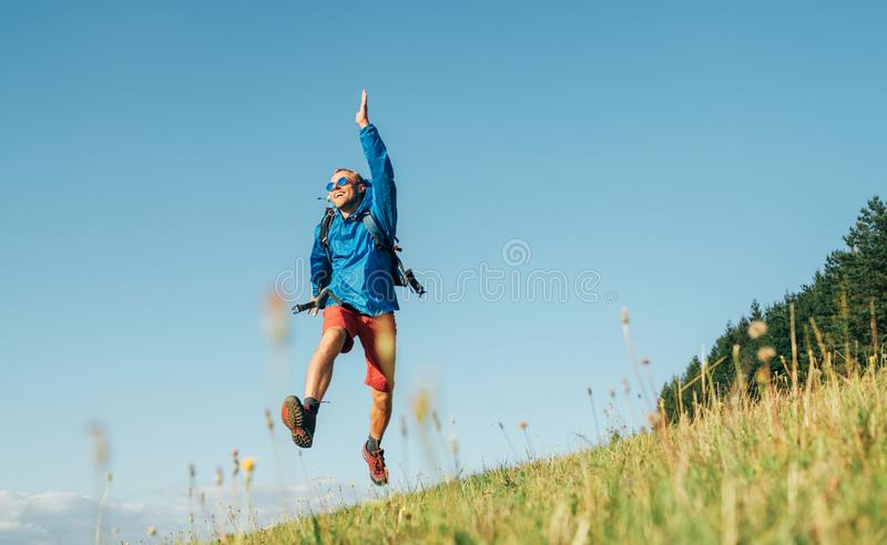 Backpacker traveler emotionally jumping over green grass mountain meadow with backpack with wide opened arms and legs. Human`s stock photo