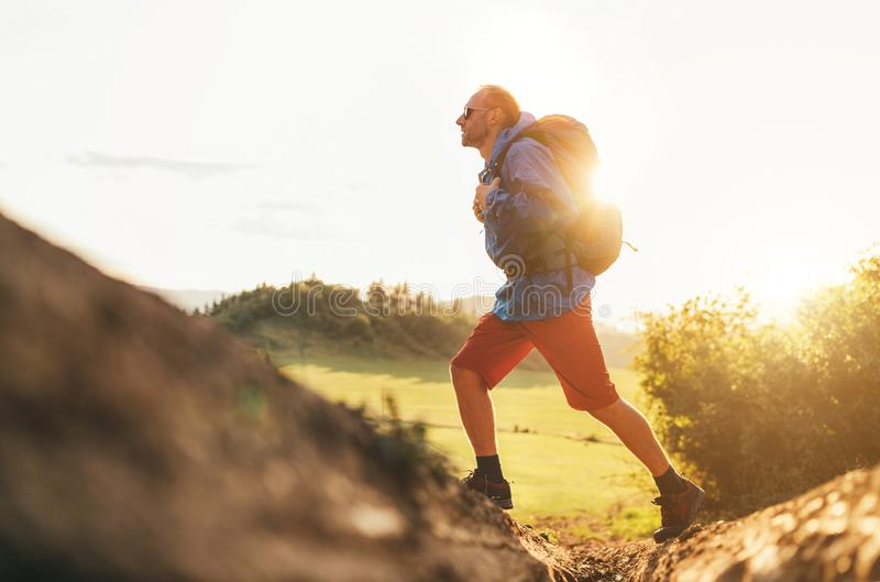 Backpacker traveler in trekking boots jumping over the ditch on mountain dirty path at summertime sunny day side shot image royalty free stock photo