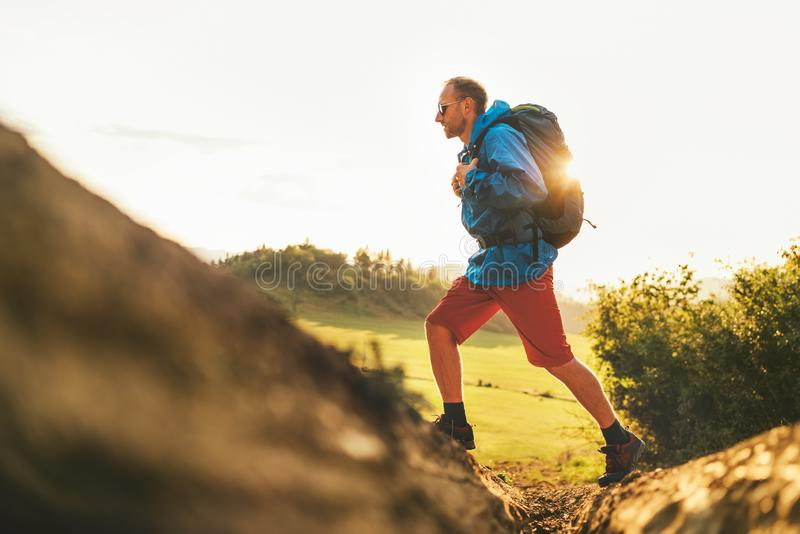 Backpacker traveler in trekking boots jumping over the ditch on mountain dirty path at summertime sunny day side shot image stock photos
