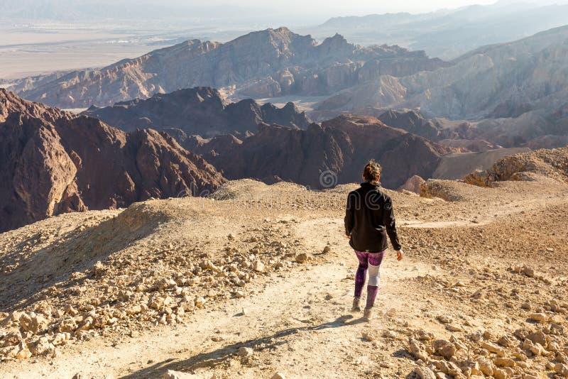 Backpacker woman descending hiking mountain ridge desert landscape. royalty free stock images