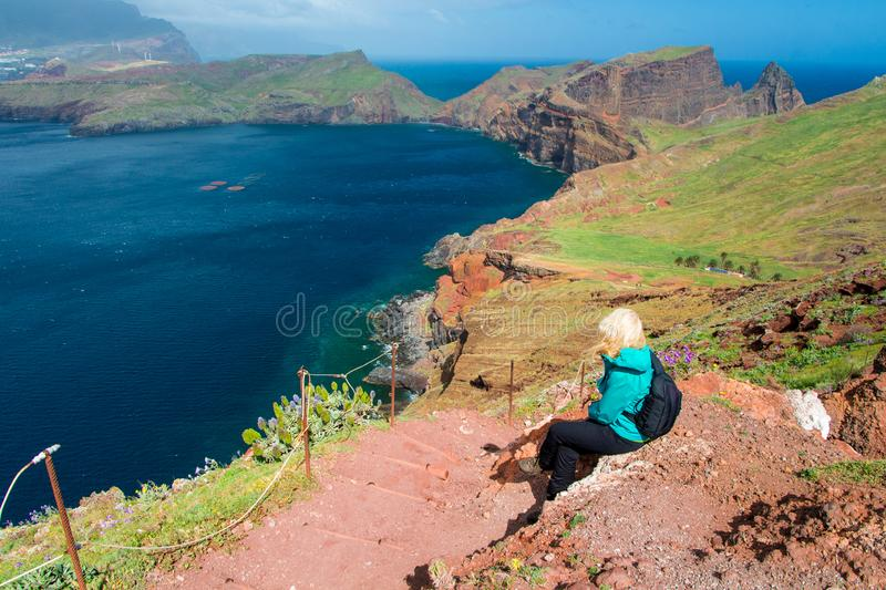 Backpacker woman sitting on a cliff royalty free stock photo