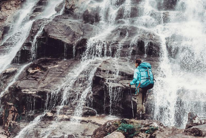 Backpacker woman and waterfall. stock image
