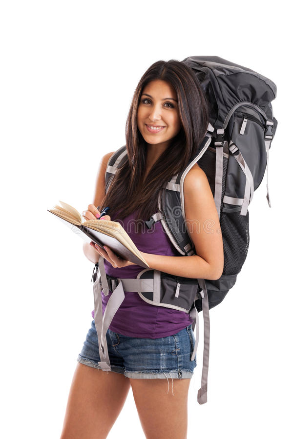 Backpacker writing in travel journal stock photo