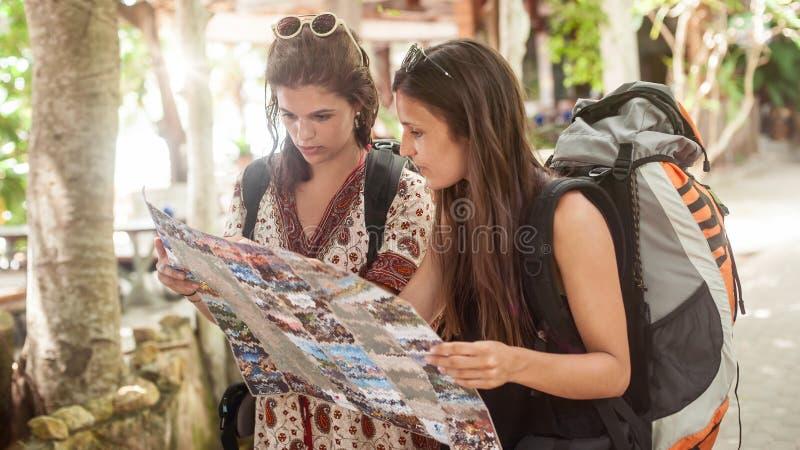 2 backpackers женщины путешественника приключения смотрят туристскую карту стоковое изображение