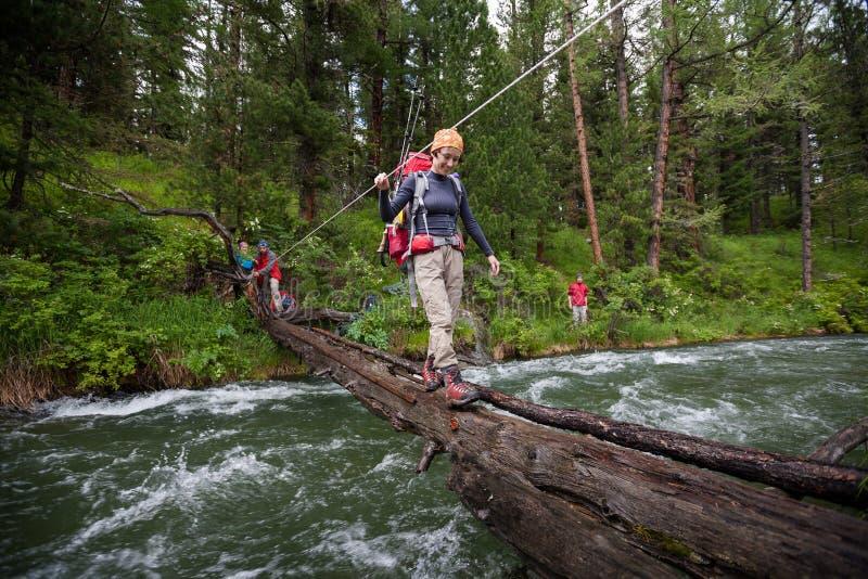 Backpackers пересекают реку горы стоковые изображения rf