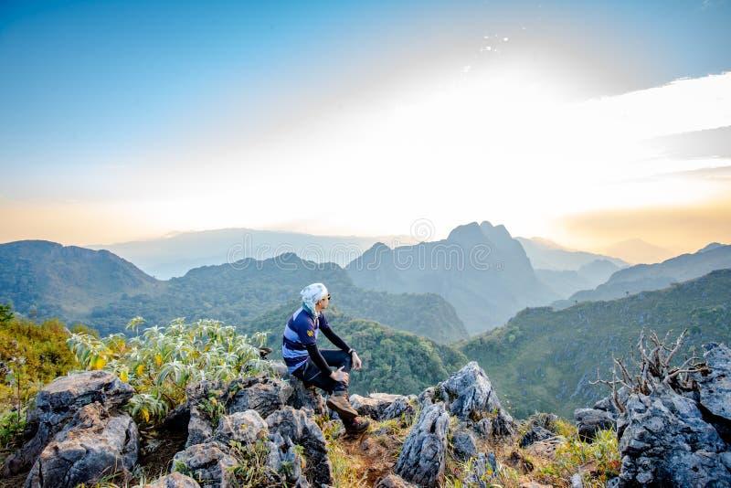 Backpackers asiáticos que emigran el cielo de oro de la puesta del sol que espera imagenes de archivo