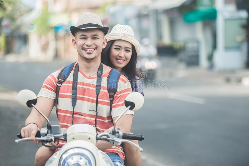 Backpackers couple riding a motorbike to start their journey. Portrait of backpackers couple riding a motorbike to start their journey stock images