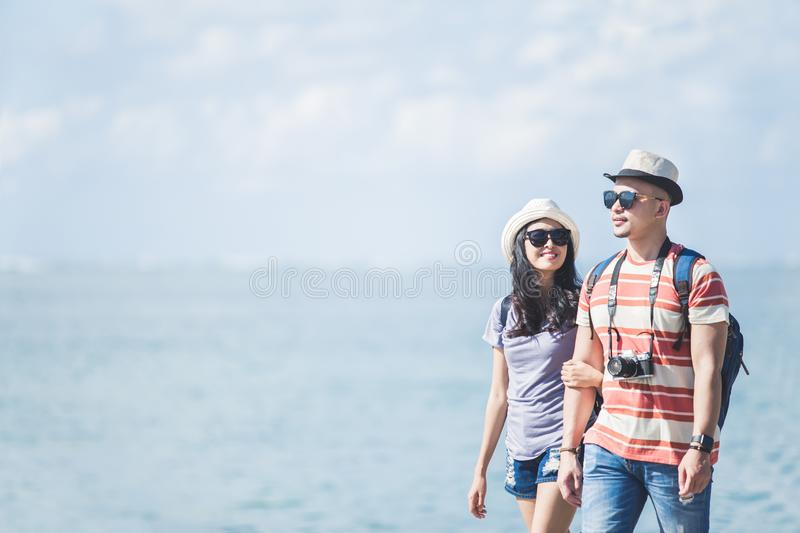 Backpackers couple wearing summer hat and sunglasses walking on royalty free stock photo
