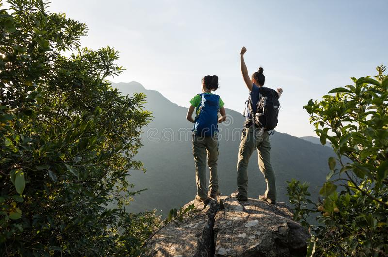 Backpackers enjoy the view on cliff edge. Two young women successful backpackers enjoy the view on cliff edge royalty free stock photo
