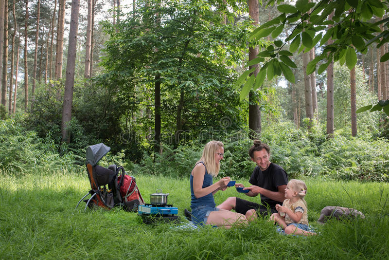 Backpackers family dining in nature. Happy family having dinner in woodland.Camping family concept stock images