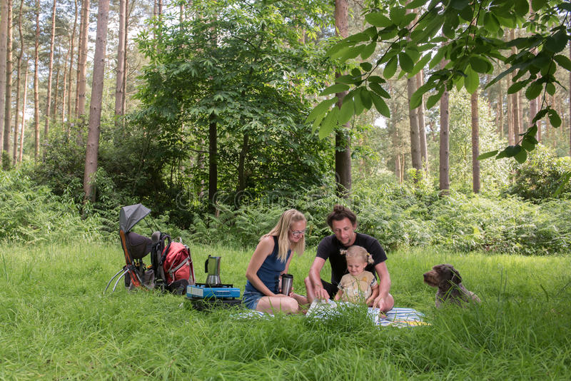 Backpackers family dining in nature. Happy family having dinner in woodland.Camping family concept stock photo