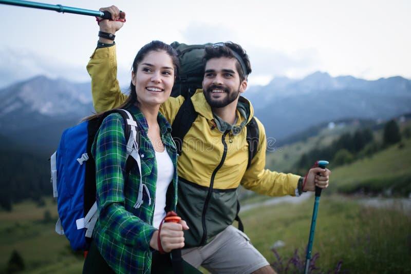Backpackers glada unga par med sticks royaltyfri bild