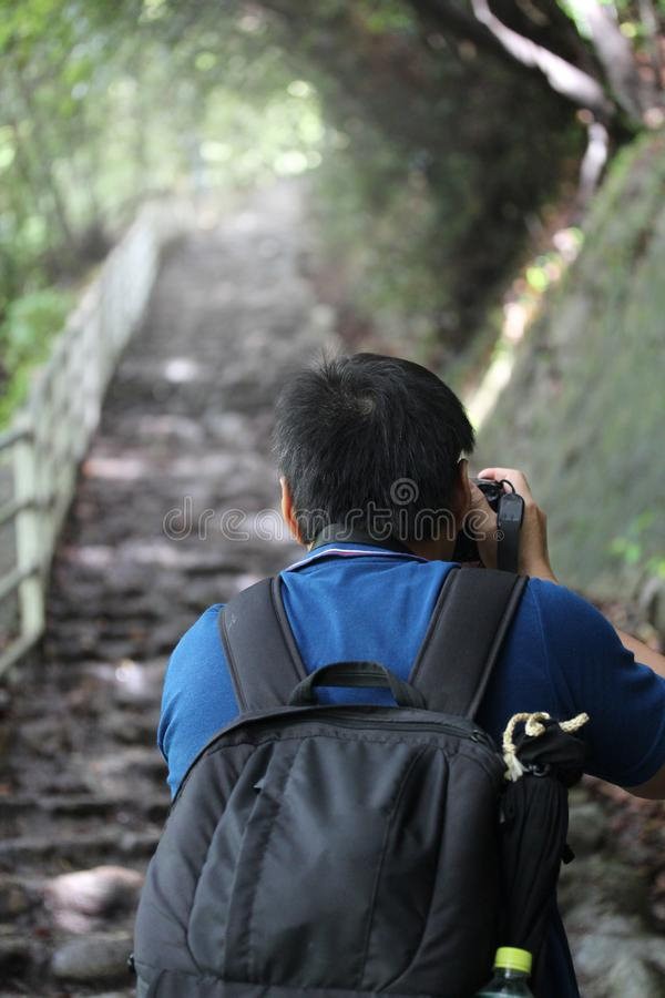 Free Backpackers Man Holding The Camera Straight Up The Stone Steps Royalty Free Stock Images - 105562019