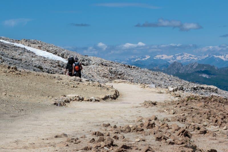 Backpackers que caminan en la trayectoria de piedra entre las montañas estériles en las montañas italianas de las dolomías en tie imagen de archivo libre de regalías