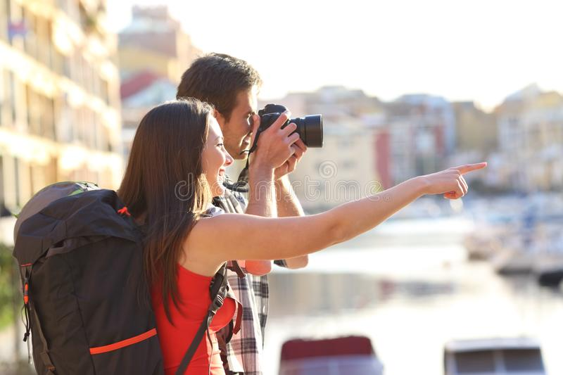 Backpackers taking photos on summer vacation. Two backpackers taking photos of landmarks on summer vacation royalty free stock image
