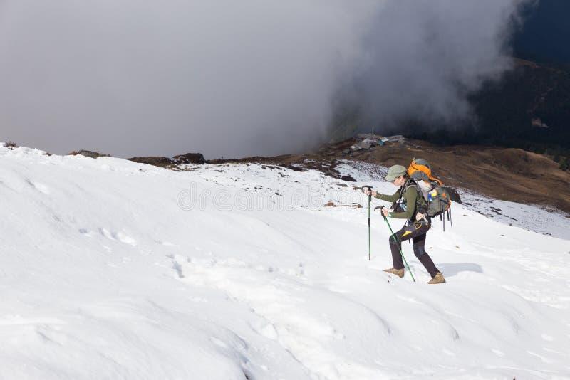 Backpackervrouw stijgende wandeling het lopen sneeuwberg royalty-vrije stock foto