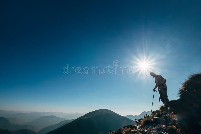 Backpackerwandelaar op het zonlicht van de bergheuvel in tegenstelling het gaan stock afbeelding