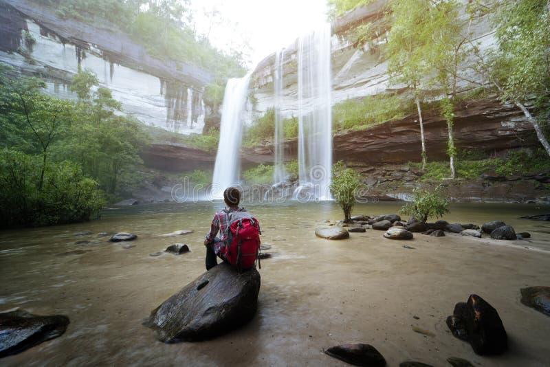 Backpackerzitting voor waterval stock foto