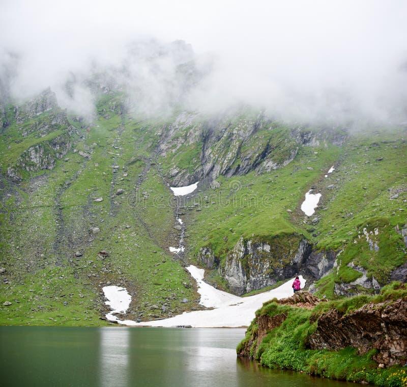 Backpacking at dam Vidraru Lake in Romania stock photography