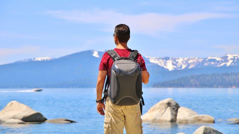 Backpacking jeziorem łódź motorowa & Śnieżne góry w tle - obrazy stock