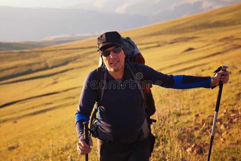 Backpakers bij zonsondergang in bergen royalty-vrije stock afbeelding
