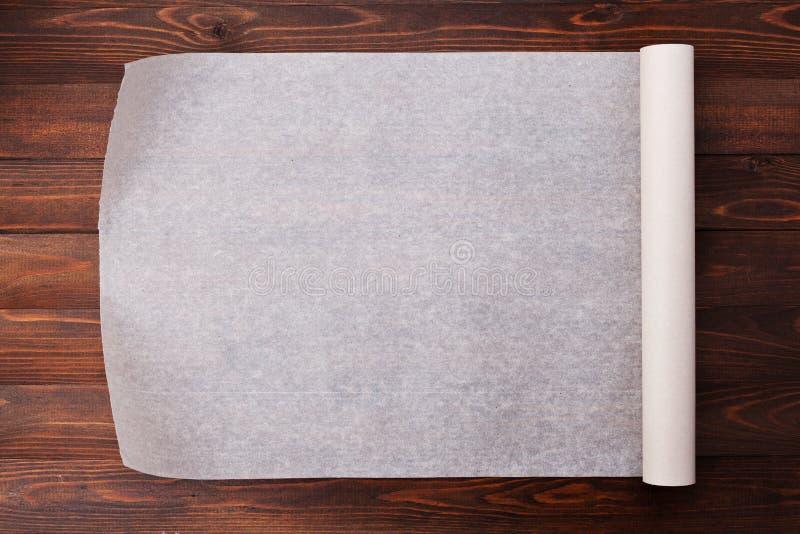 Backpapier auf hölzernem Küchentisch für Menü oder Rezepte lizenzfreie stockfotos