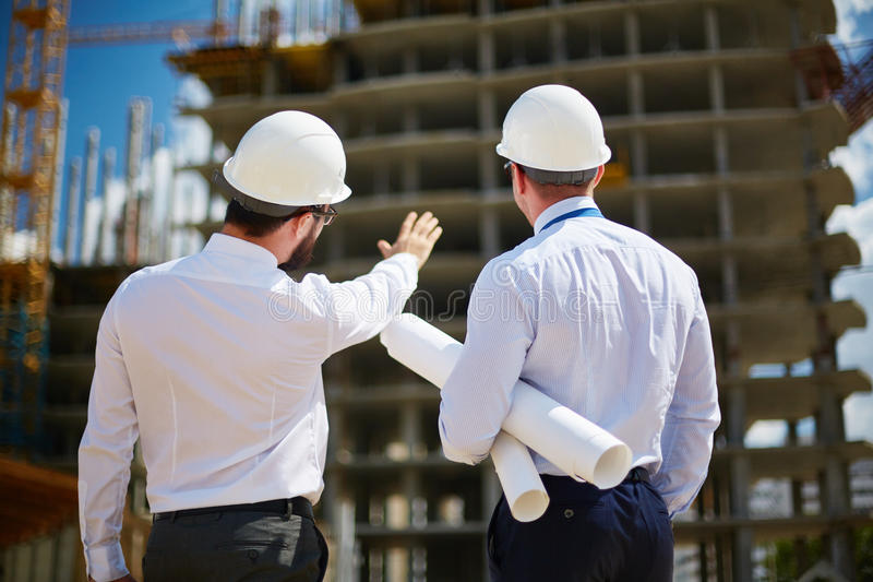 Backs of architects. Rear view of architects looking at construction royalty free stock photo