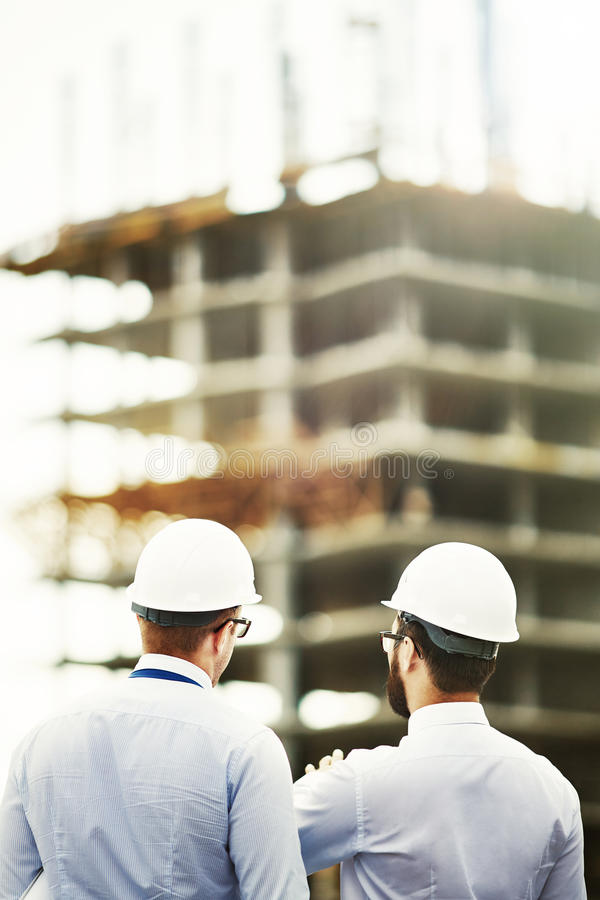 Backs of architects. Two colleagues in helmets looking at new building construction stock image