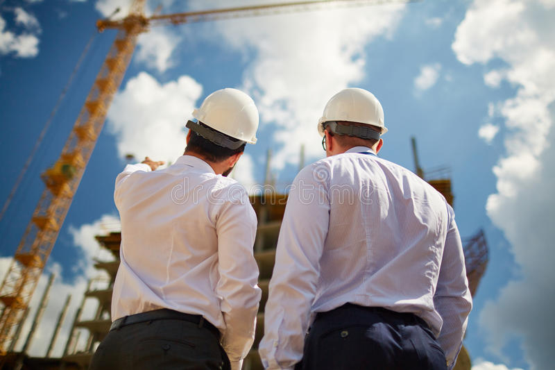 Backs of engineers. Male architects in helmets discussing new construction while standing in front of it stock photo