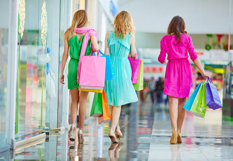 Backs of shoppers. Group of shoppers carrying paperbags royalty free stock image