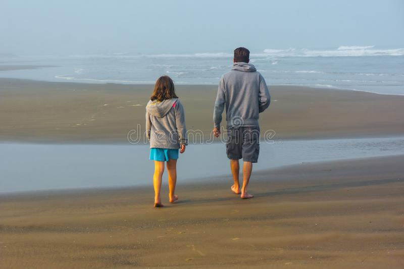 Father Daughter Stroll Beach in Quiet Conversation royalty free stock photography