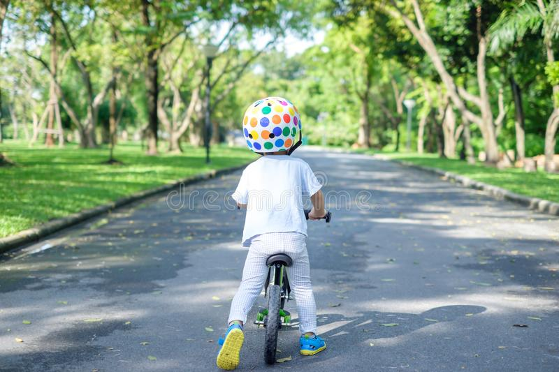 Backside of Asian 2 years toddler boy child wearing safety helmet learning to ride first balance bike royalty free stock photo
